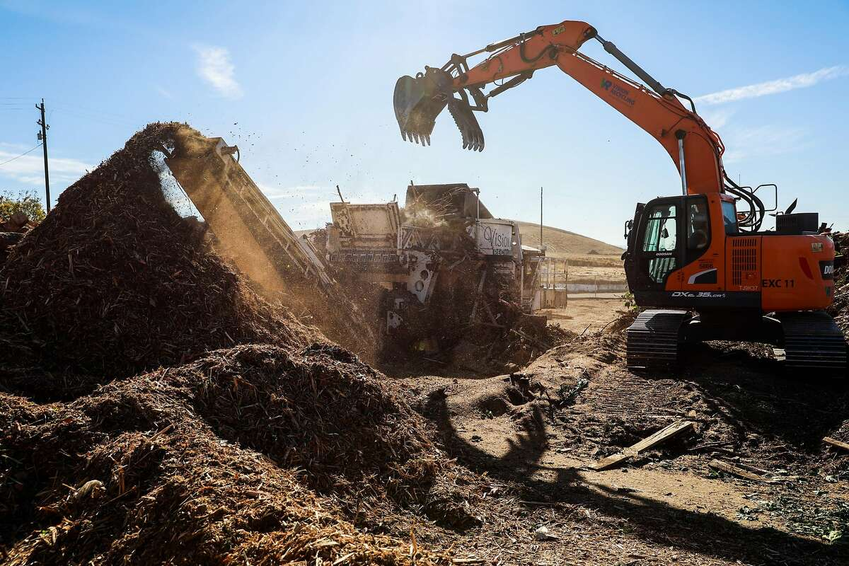 Machine operator Oscar Romo (right) dumps branches into a processor to become wood mulch at Vision Recycling in Livermore in November. Some firefighters are concerned about the use of such materials near homes.