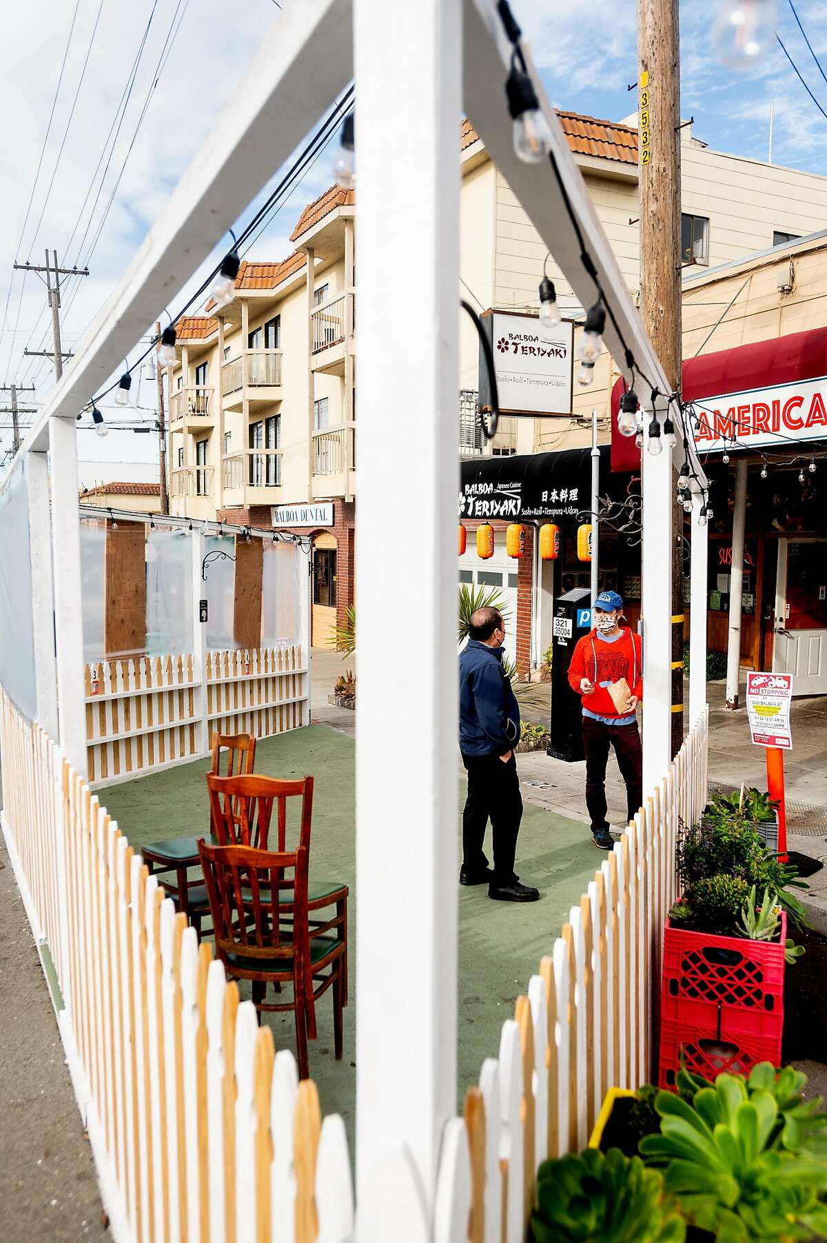 Alec Hawley (right) speaks with Eat Americana owner Tony Lai inside a parklet he designed for the restaurant.