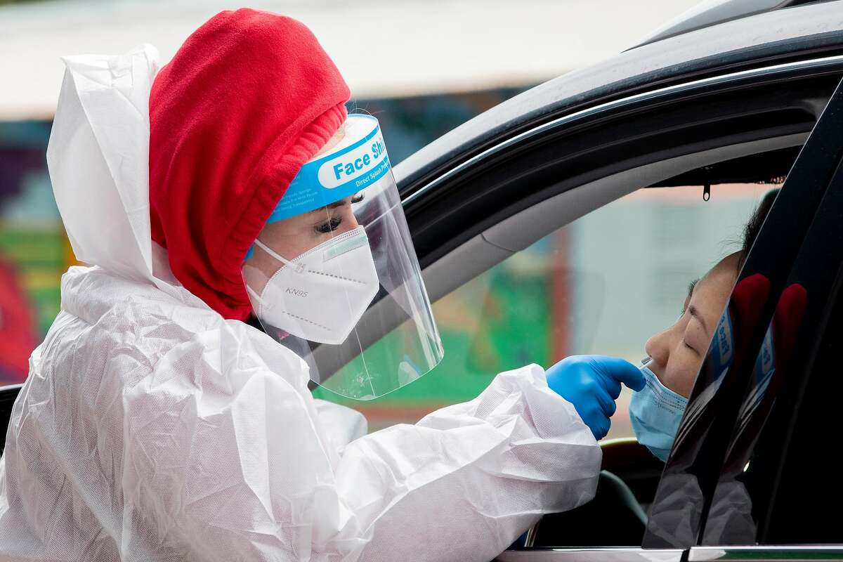 A worker administers a coronavirus test at a new drive-through test site at San Francisco's Alemany Farmers' Market.