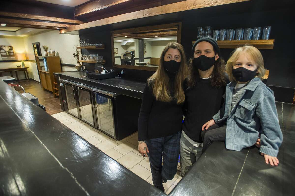 Lisa Kuznicki, left, Evan Sumrell, center, and their son Stanley, right, pose for a portrait Wednesday, Nov. 25, 2020 inside Aster, the family's new farm-to-table restaurant located at 134 Ashman St. in downtown Midland. (Katy Kildee/kkildee@mdn.net)