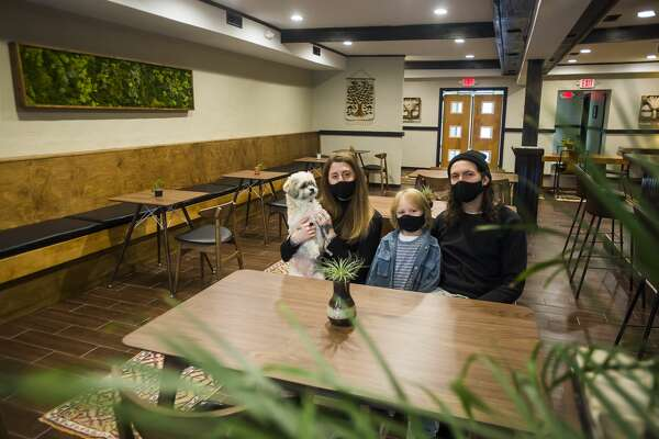 Lisa Kuznicki, left, Evan Sumrell, right, and their son Stanley, center, pose for a portrait Wednesday, Nov. 25, 2020 inside Aster, the family's new farm-to-table restaurant located at 134 Ashman St. in downtown Midland. (Katy Kildee/kkildee@mdn.net)