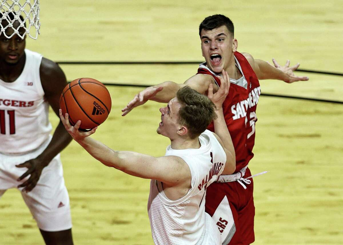 PISCATAWAY, NEW JERSEY - NOVEMBER 25: Oskar Palmquist #1 of the Rutgers Scarlet Knights is fouled by Matas Spokas #23 of the Sacred Heart Pioneers during the season opening game at Rutgers Athletic Center on November 25, 2020 in Piscataway, New Jersey. (Photo by Elsa/Getty Images)