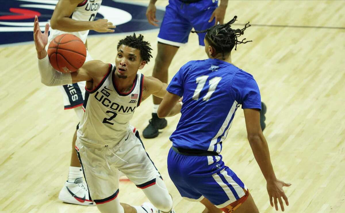 UConn guard James Bouknight (2) battles for a loose ball against Central Connecticut State guard Tre Mitchell (11) on Wednesday.