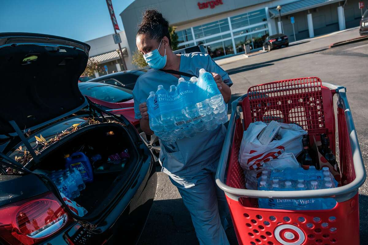 Nicole Johnson loads her car with bottled water from a Target shopping run in Sausalito Wednesday.