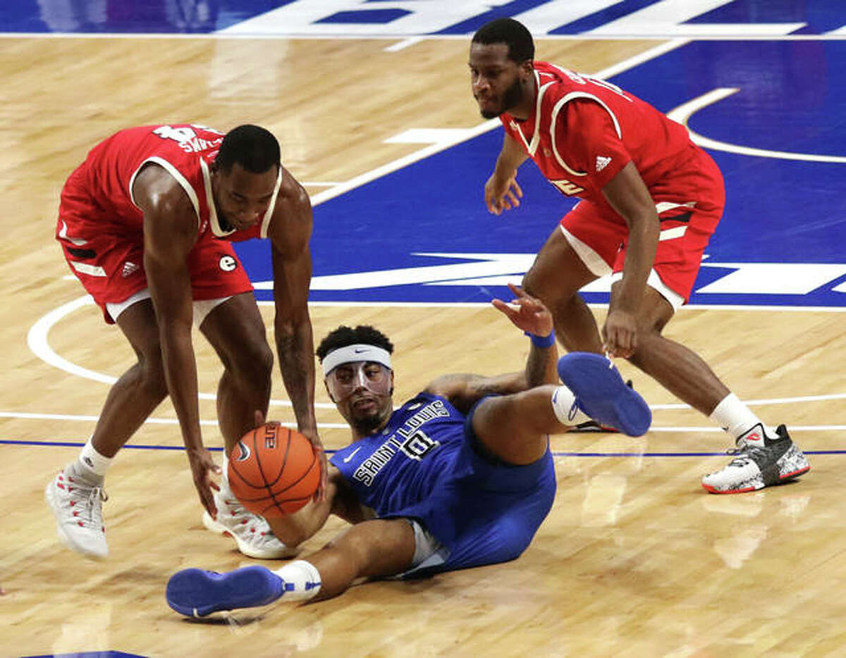 SIUE's Cam Williams (left) comes up with the loose ball after a failed steal attempt by SLU's Jordan Goodwin on Wednesday night at Chaifetz Arena in St. Louis. SIUE's Courtney Carter (right) watches the play.