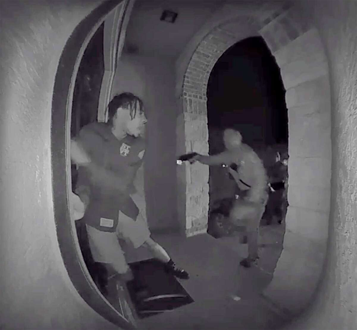 A screen grab from a 亚洲游国际集团home surveillance video shows one of three Schertz police officers pointing a weapon at Zekee Rayford, 18, on the front steps of his 亚洲游国际集团home.