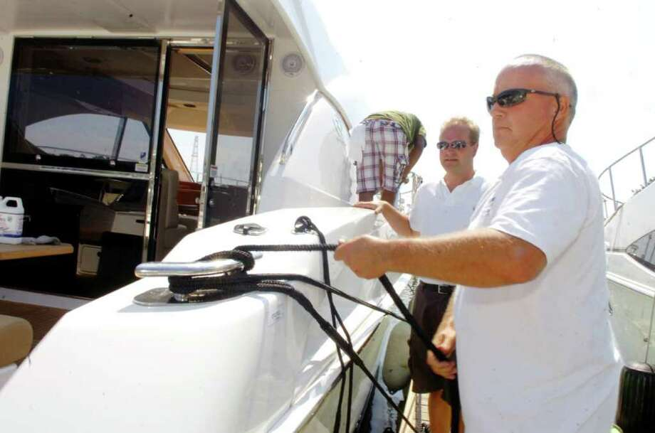 Bill Biebel, right, a broker at Southpaw Yacht Sales at Palmer Point Marina, left, and Magnus Lejdstrom, the owner of Southpaw Yacht Sales, secure one of their yachts for the upcoming storm, on Thursday, Sept. 2, 2010 Photo: Helen Neafsey / Greenwich Time