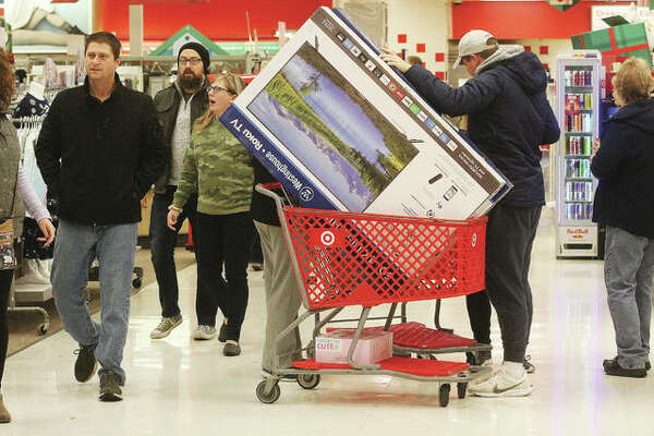 Customers walk one of the main aisles at the Alton Target store last year during the start of the holiday shopping season. Because of COVID-19, this year will be very different, with few stores open on Thursday, month-long sales in an attempt to reduce crowd surges and an emphasis on online sales.