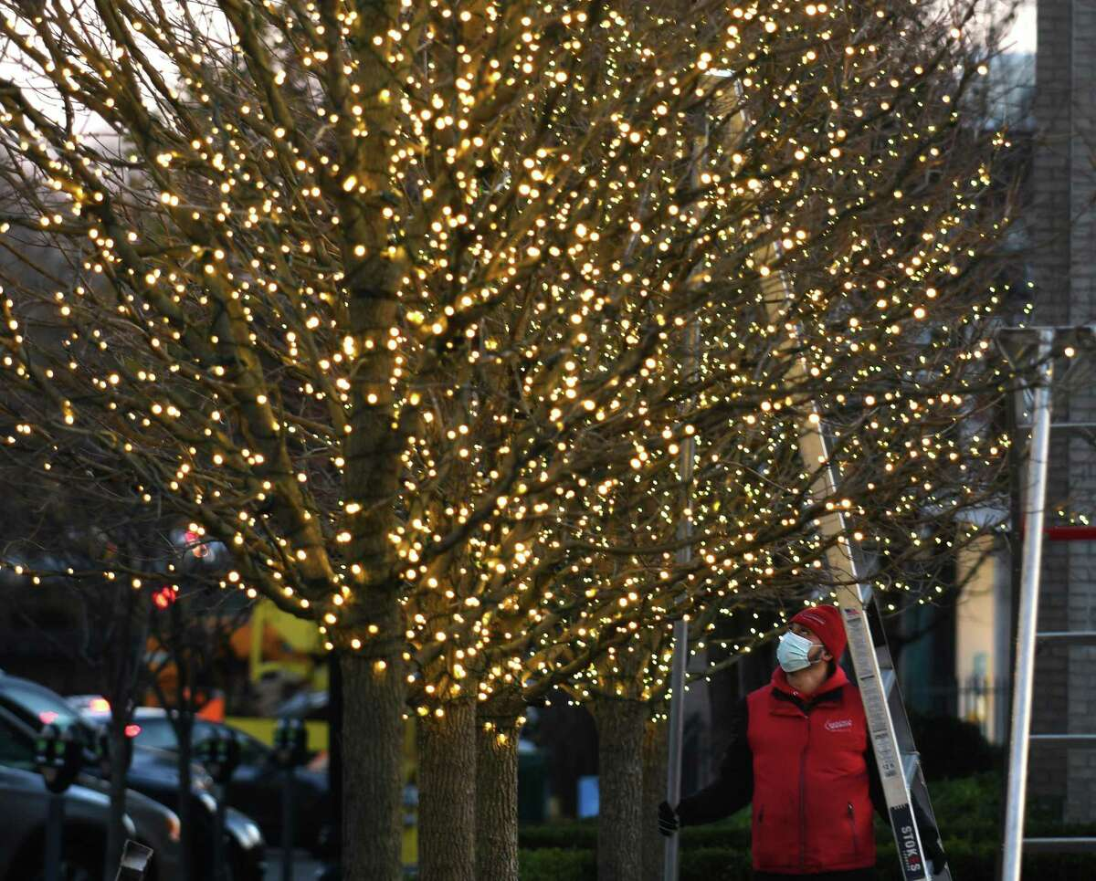 Marvin Velasquez, of Christmas Lighting Company, installs strings of lights on the trees outside Restoration Hardware in downtown Greenwich, Conn. Tuesday, Nov. 24, 2020. The private effort behind those lights is now looking to bring American flags to Greenwich Avenue.