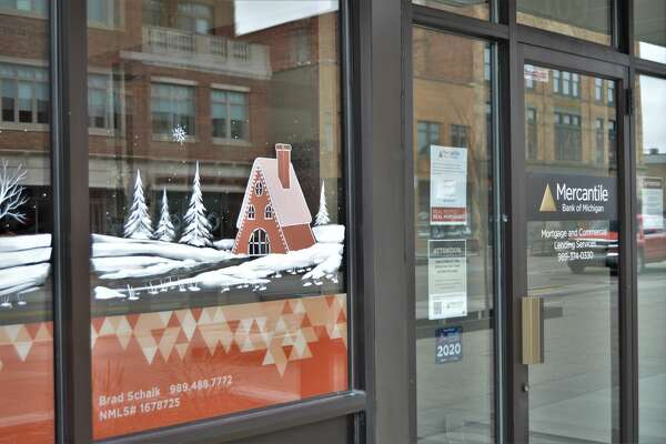 Businesses in downtown Midland are looking festive with painted designs by Brush Monkeys of Ann Arbor. (Ashley Schafer/ashley.schafer@hearstnp.com)