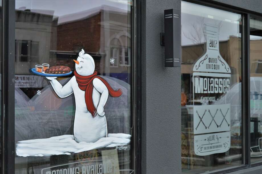 Businesses in downtown Midland are looking festive with painted designs by Brush Monkeys of Ann Arbor. (Ashley Schafer/ashley.schafer@hearstnp.com) Photo: Ashley Schafer