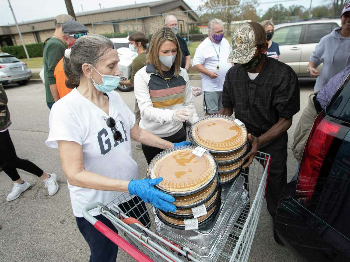 BJ Bradley, left, helps offload pies with Keely Brewer for the annual Friends Feeding Friends Thanksgiving meal, Thursday, Nov. 26, 2020, in Conroe. Volunteers handed out 1,500 meals to community members.