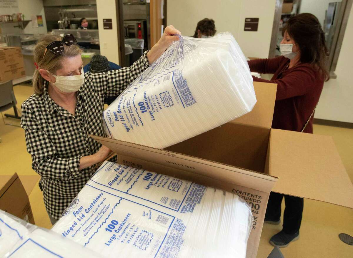 Carol Bledsoe helps unpack to-go containers as for the annual Friends Feeding Friends Thanksgiving meal, Thursday, Nov. 26, 2020, in Conroe. Volunteers handed out 1,500 meals to community members.