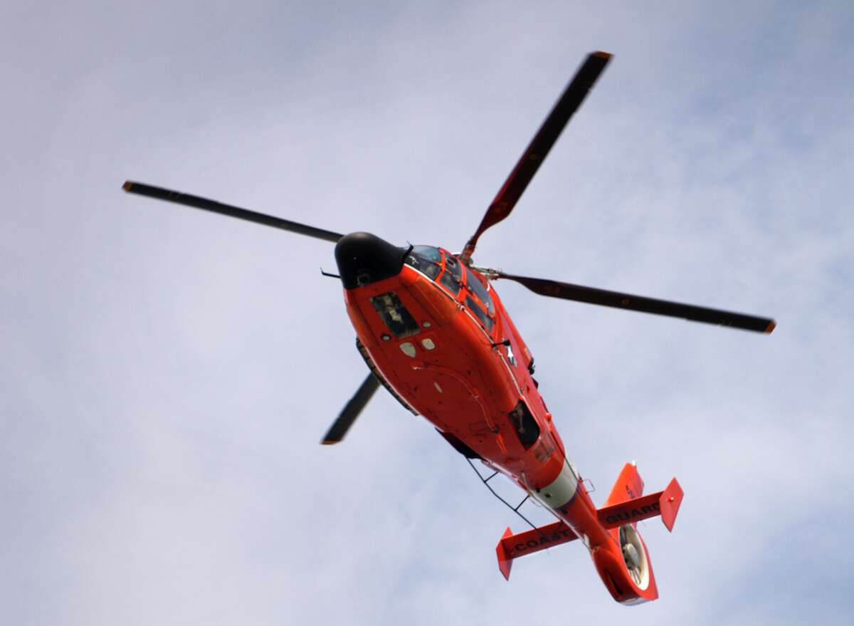 FILE - A U.S. Coast Guard helicopter flies over San Francisco. Three people and two dogs were rescued by the Coast Guard on Wednesday morning near Concord after their boat was stranded.