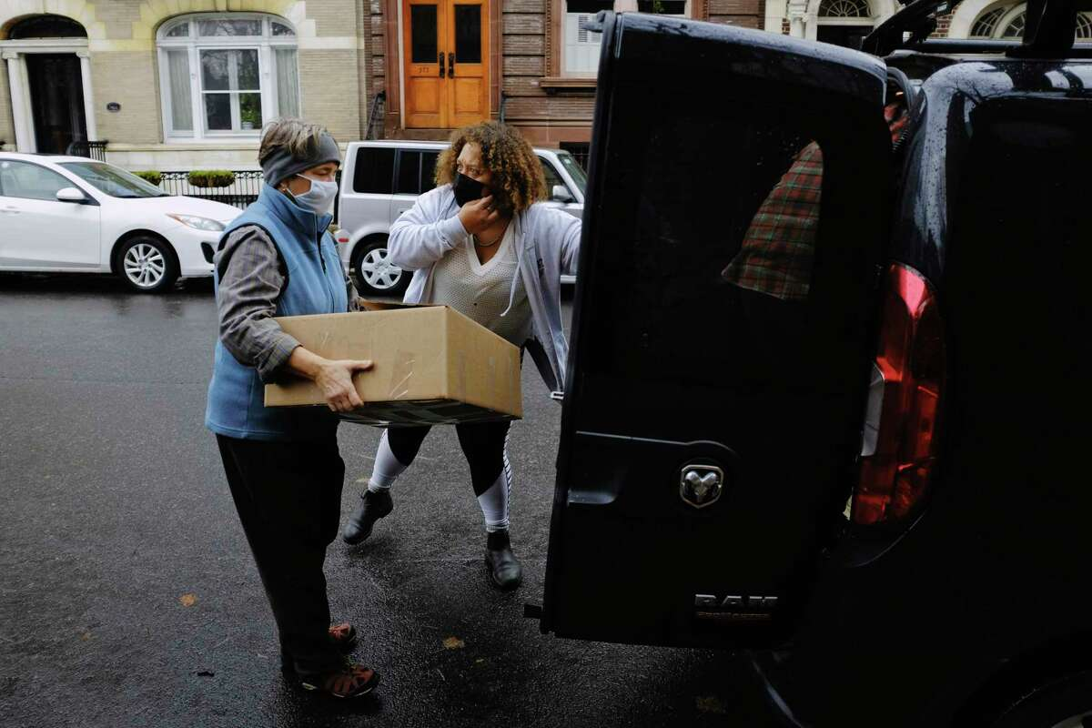 Equinox volunteer Lynne Lekakis, left, loads a box of turkey dinners into the vehicle of Jammella Anderson, right, who runs the Free Food Fridge, on Thursday, Nov. 26, 2020, in Albany, N.Y. Due to the pandemic Equinox did not host their Thanksgiving Day meal at the First Presbyterian Church and had the majority of their meals were delivered to people's homes. But to make sure that everyone who wanted a meal could get one the organization also had the van with meals parked outside the church for those in the area who showed up. Anderson, who had already delivered 450 meals, working with Feed Albany and the Honest Weight Food Co-op, took the box of additional meals to deliver to those in need. (Paul Buckowski/Times Union)