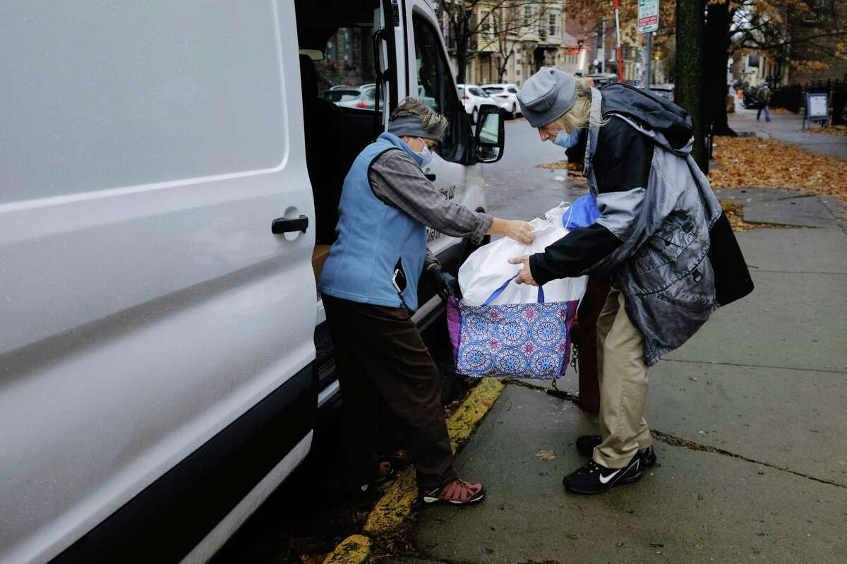 Equinox volunteer Lynne Lekakis hands out turkey dinners from a van parked outside the First Presbyterian Church on Thursday, Nov. 26, 2020, in Albany, N.Y. Due to the pandemic Equinox did not host their Thanksgiving Day meal at the church and had the majority of their meals were delivered to people's homes. But to make sure that everyone who wanted a meal could get one the organization also had the van with meals parked outside the church for those in the area who showed up. (Paul Buckowski/Times Union)