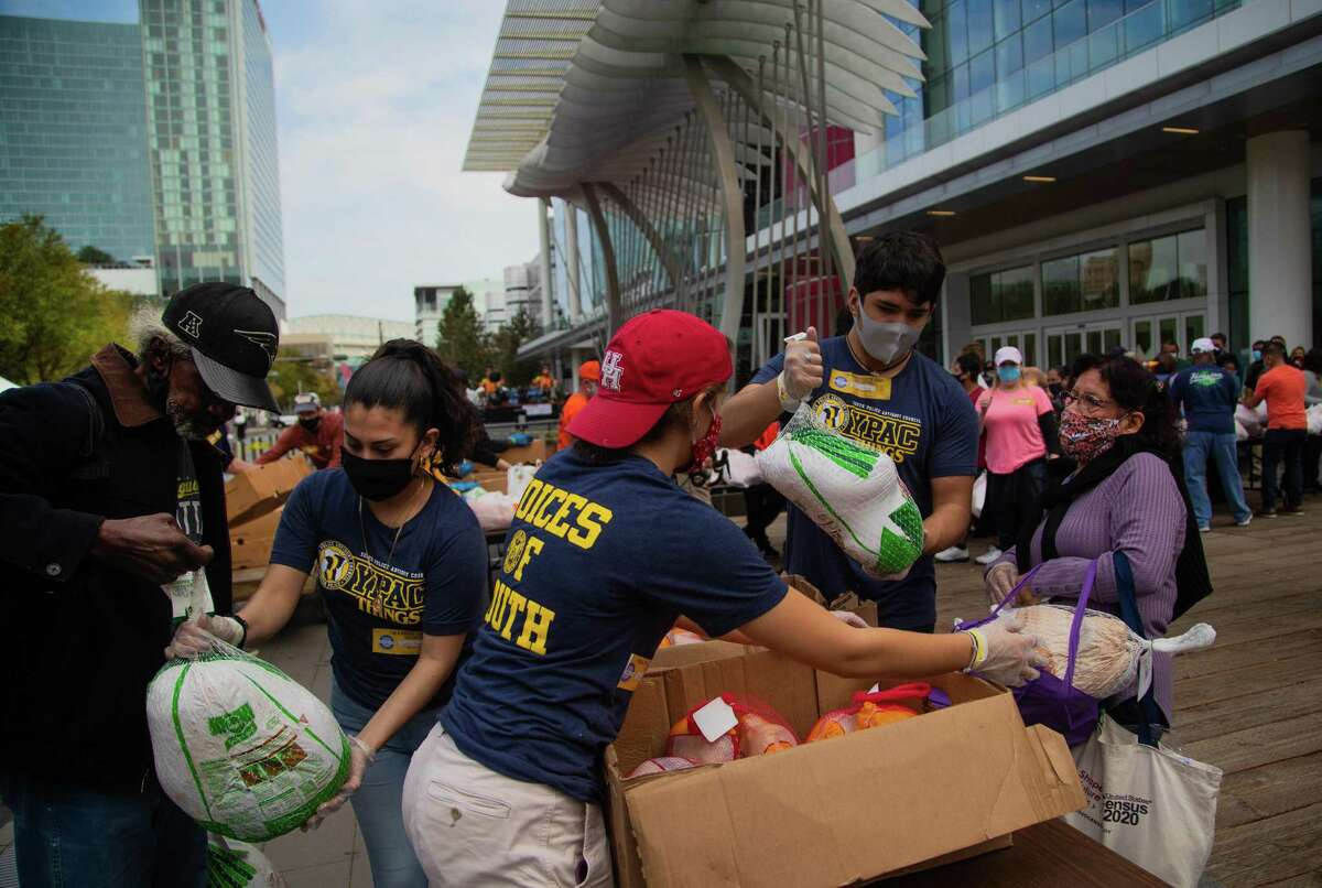 Volunteers at the 42nd annual Super Feast at George R. Brown Convention Center distribute food during the event, Thursday, Nov. 26, 2020, in Houston. Because of the COVID-19 pandemic, the event took place outdoors.
