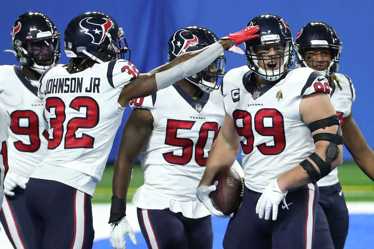 Houston Texans defensive end J.J. Watt (99) celebrates his interception of a pass by Detroit Lions quarterback Matthew Stafford for a touchdown during the first quarter of an NFL football game at Ford Field Thursday, Nov. 26, 2020, in Detroit. Watt batted the ball down and hauled it in for the interception.