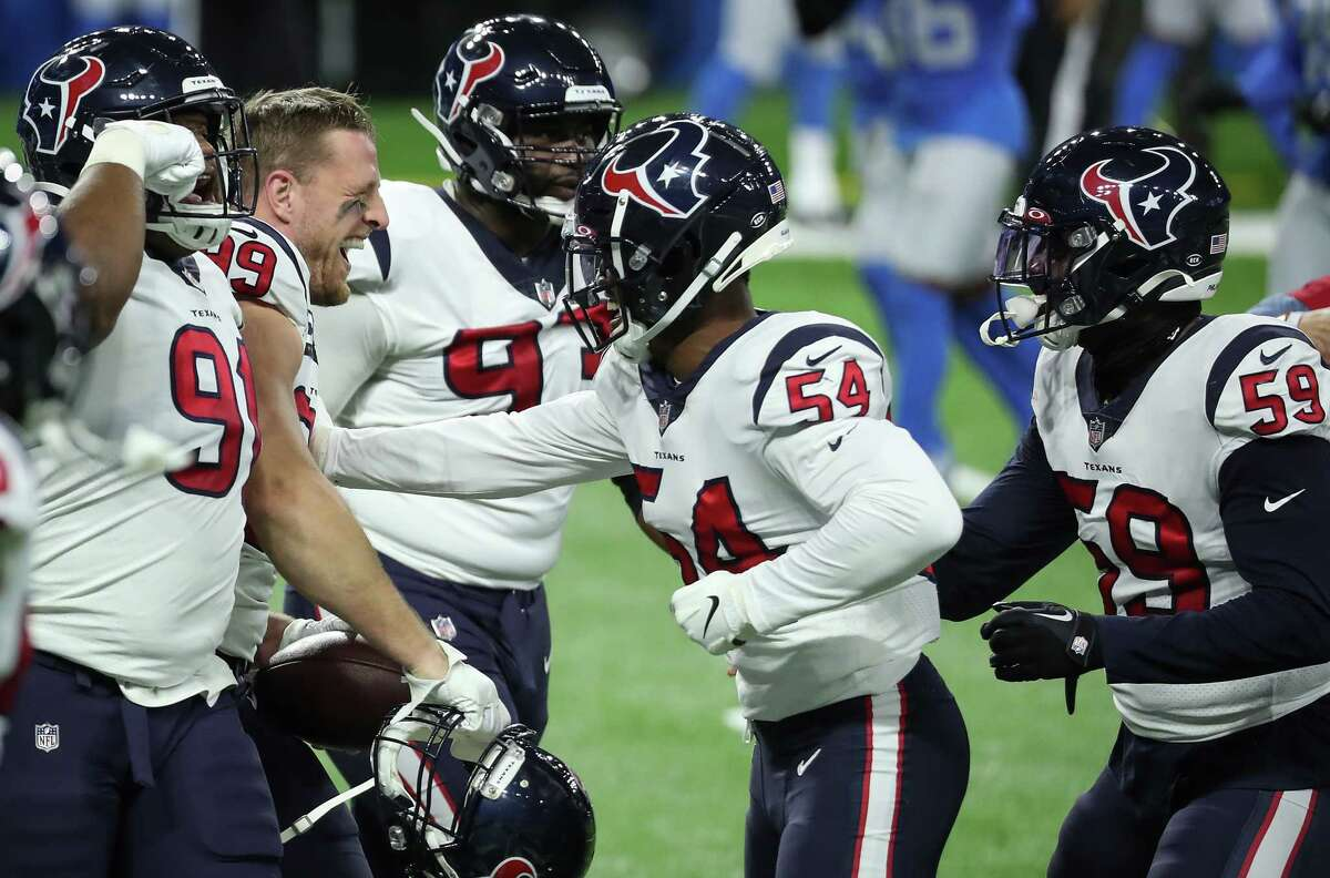 Houston Texans defensive end J.J. Watt (99) and linebacker Jake Martin (54) celebrate Watt's interception of a pass by Detroit Lions quarterback Matthew Stafford for a touchdown during the first quarter of an NFL football game at Ford Field Thursday, Nov. 26, 2020, in Detroit. Watt batted the ball down and hauled it in for the interception.