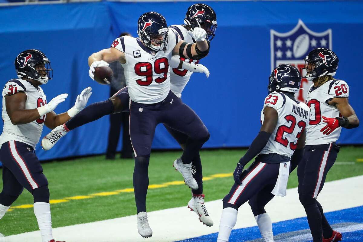 Houston Texans defensive end J.J. Watt (99) and Houston Texans defensive end Charles Omenihu (94) celebrate Watt's interception of a pass by Detroit Lions quarterback Matthew Stafford for a touchdown during the first quarter of an NFL football game at Ford Field Thursday, Nov. 26, 2020, in Detroit. Watt batted the ball down and hauled it in for the interception.