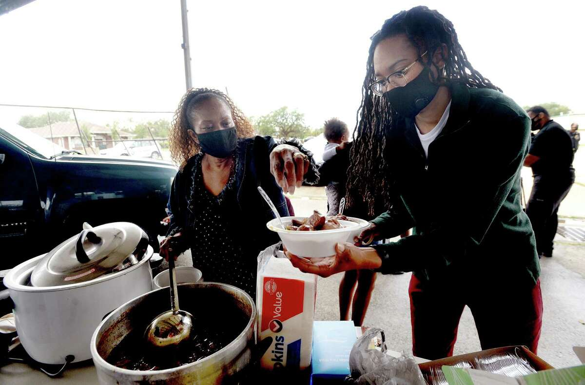 Gloria Garrison (left) and family, including Britany Kinlaw, gather round to serve up homemade gumbo to the homeless at an encampment on 9th Avenue in Port Arthur Thursday afternoon. Photo taken Thursday, November 26, 2020 Kim Brent/The Enterprise