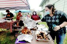 Jacqueline Hays uncovers onne of the main attractions as she, neighbors and friends hold a socially distanced backyard picnic to safely celebrate Thanksgiving in the joint backyard of their Old Town residences. Photo taken Thursday, November 26, 2020 Kim Brent/The Enterprise