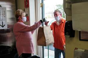 Heather Carolan, a volunteer from the Devon Rotary Club, gives out a Thanksgiving Day dinner to Tim Duhaime at Beth-El Center, Inc. in Milford, Conn., on Thursday Nov. 26, 2020. A traditional Thanksgiving dinner of turkey, stuffing and side dishes were prepared and donated by Dockside Brewery in Milford.