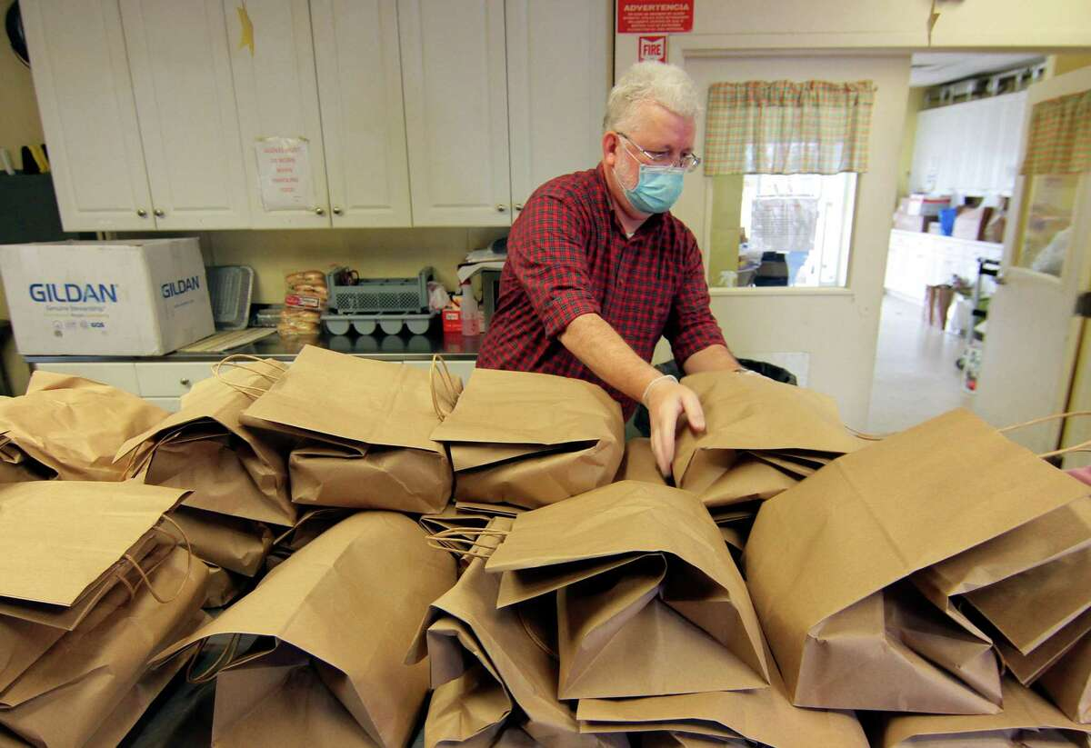 Mark Davis, a volunteer from the Devon Rotary Club, organizes Thanksgiving Day dinners to be given out at Beth-El Center, Inc. in Milford, Conn., on Thursday Nov. 26, 2020. A traditional Thanksgiving dinner of turkey, stuffing and side dishes were prepared and donated by Dockside Brewery in Milford.