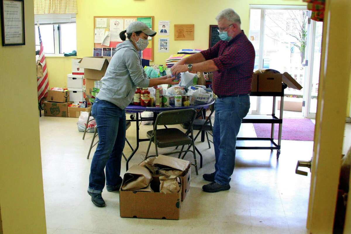 Beth-El Center, Inc. volunteer Virginia Pitzer, left, and Mark Davis, a volunteer from the Devon Rotary Club, load up Thanksgiving Day dinners to be delivered to local residents by Virginia in Milford.