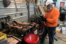"""Mike Oberloier of Beaverton works on the 1901 """"type O"""" Thew model steam-powered shovel'sswing/travel motorin his home machine shop in Beaverton. (Photo provided/Mike Oberloier)"""