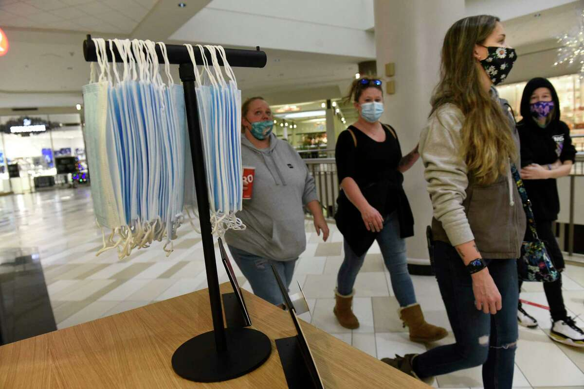 Black Friday holiday shoppers walk past a store that is providing face masks for their customers Crossgates Mall on Friday, Nov. 27, 2020 in Guilderland, N.Y. (Lori Van Buren/Times Union)