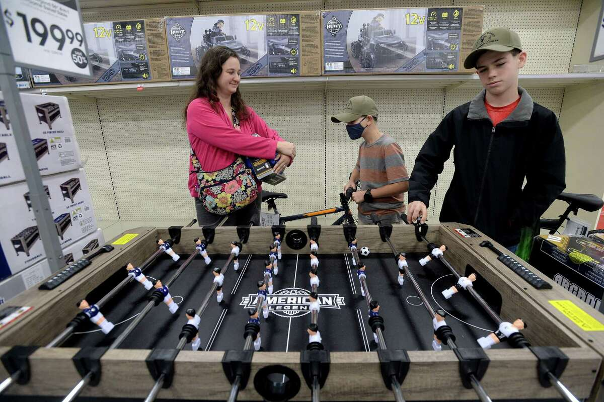 Tricia Cooper talks with sons Keagan (center) and Luke Cooper as they wait for assistance with a 4-in-1 swivel game table at Academy Sports and Outdoors on Black Friday. With several upcoming bbirthdays, Cooper said the Black Friday deals were a good way to stay on budget. The Coopers celebrated Thanksgiving Wednesday as a family member was called in to work Thursday.