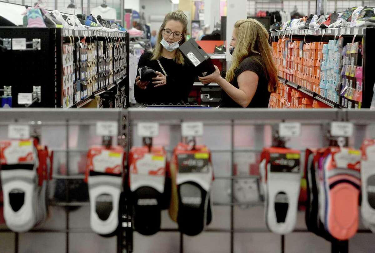 Sisters Amanda Enderle (left) and Stephanie Travis shop for shoes during the pre-dawn opening at Academy Sports and Outdoors on Black Friday. The pair have been Black Friday shoppers together for over 13 years.