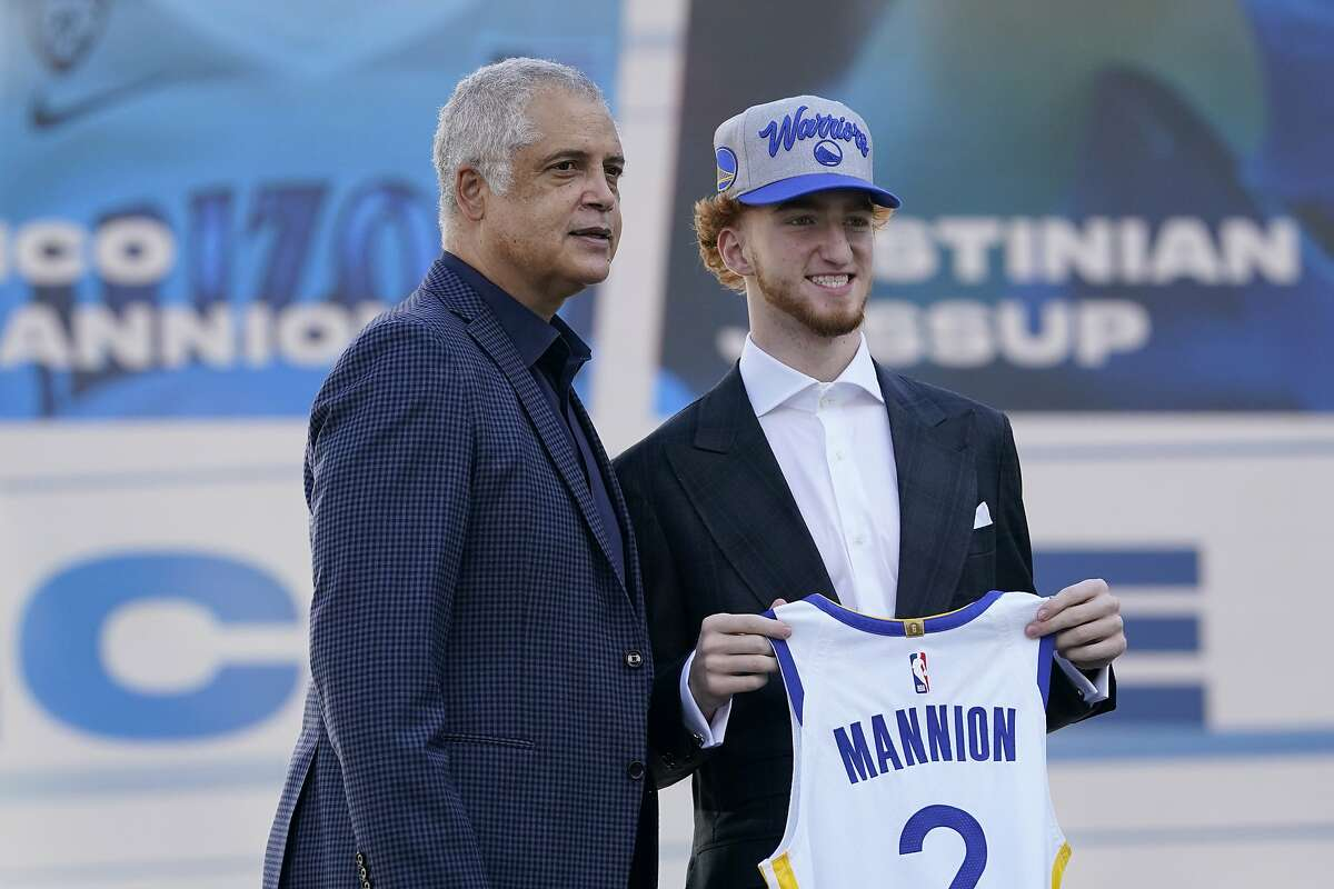 Golden State Warriors draft pick Nico Mannion, right, poses next to agent Bill Duffy in San Francisco, Thursday, Nov. 19, 2020. (AP Photo/Jeff Chiu)