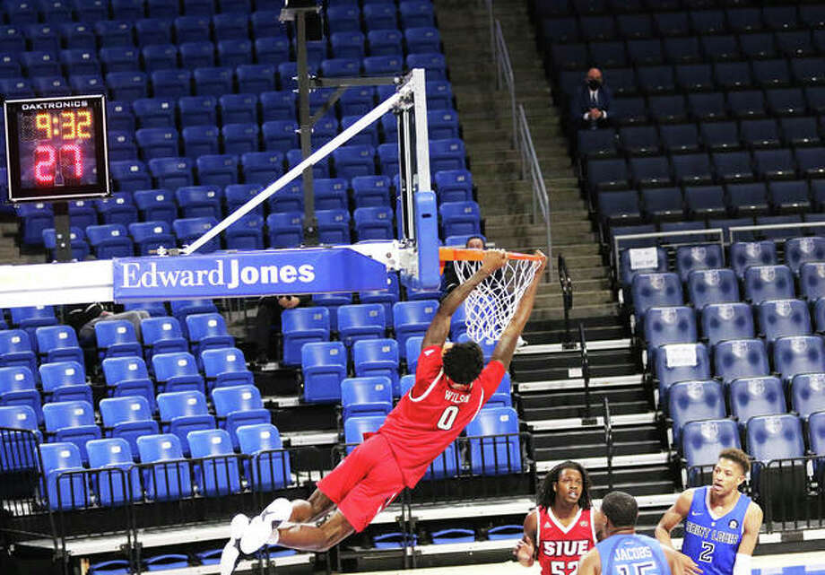 SIUE's Sidney Wilson holds onto the rim after dunking on a break during the second half of the Cougars' season opener against Saint Louis on Wednesday night at Chaifetz Arena in St. Louis. Photo: Greg Shashack / The Telegraph