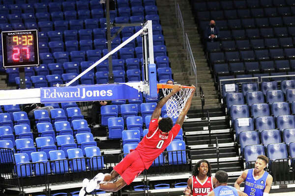 SIUE's Sidney Wilson holds onto the rim after dunking on a break during the second half of the Cougars' season opener against Saint Louis on Wednesday night at Chaifetz Arena in St. Louis.
