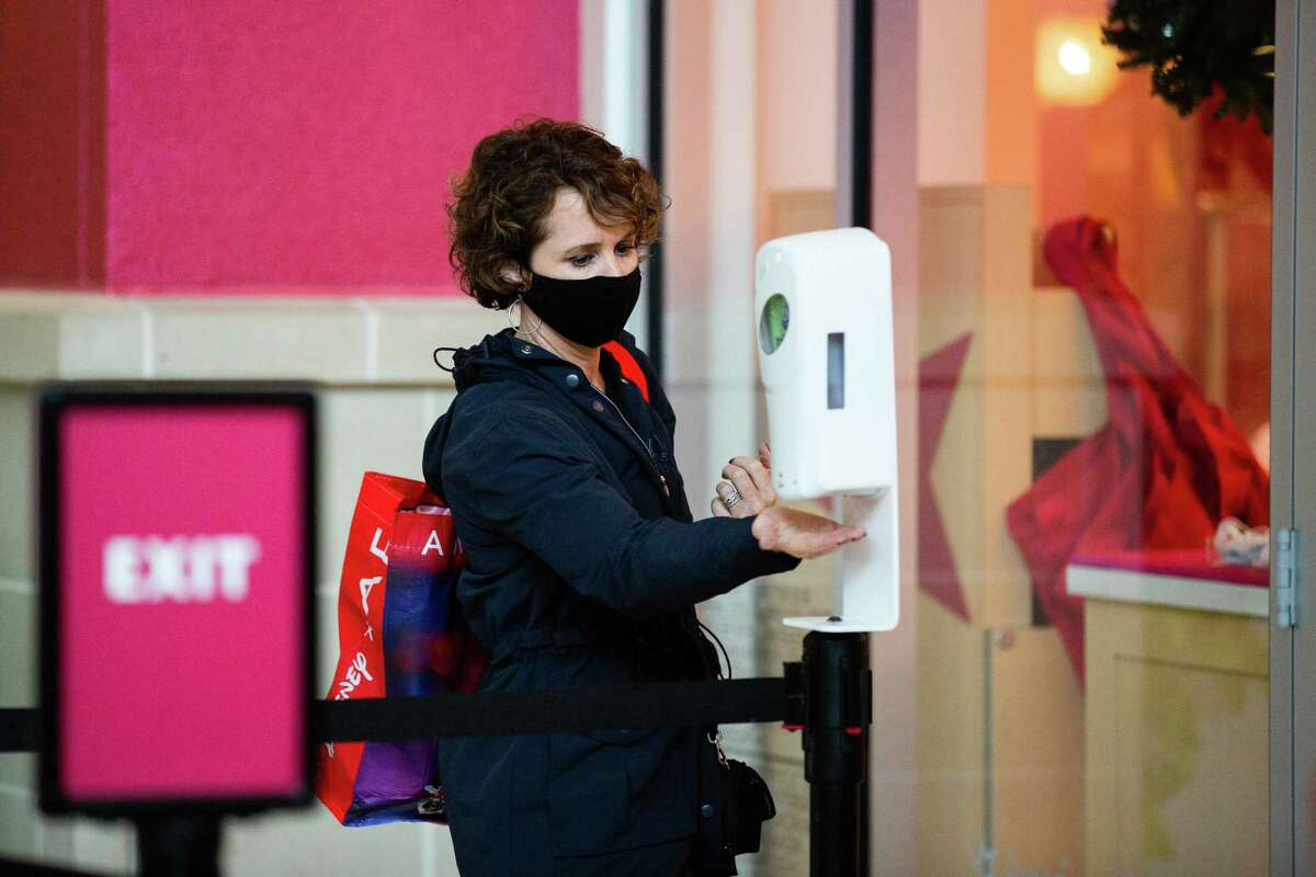 Before entering American Girl at Memorial City Mall, a shopper gets hand sanitizer, Friday, Nov. 27, 2020, in Houston.