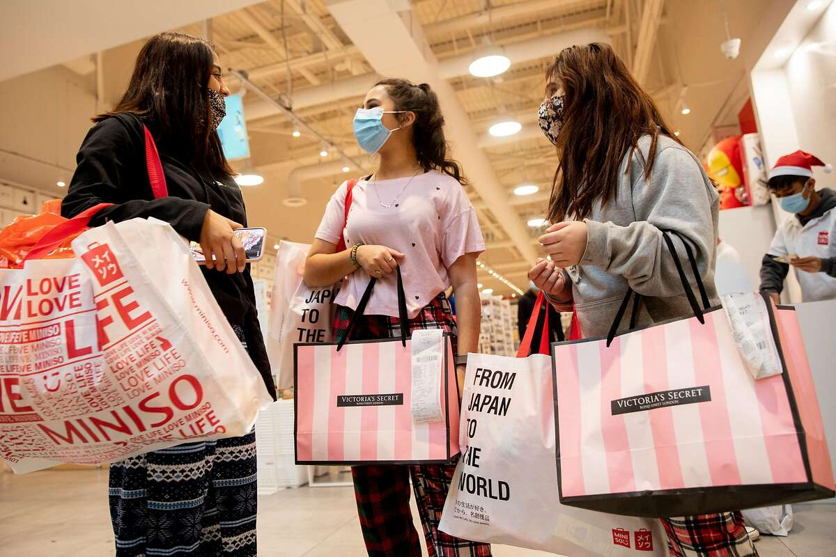 (From left) Aliya Bassa, 17, Sue Bassa, 18, and Fatima Nakhuda, 16, of Marin wear face masks while shopping at Victoria's Secret during the Black Friday rush in the Great Mall in Milpitas.