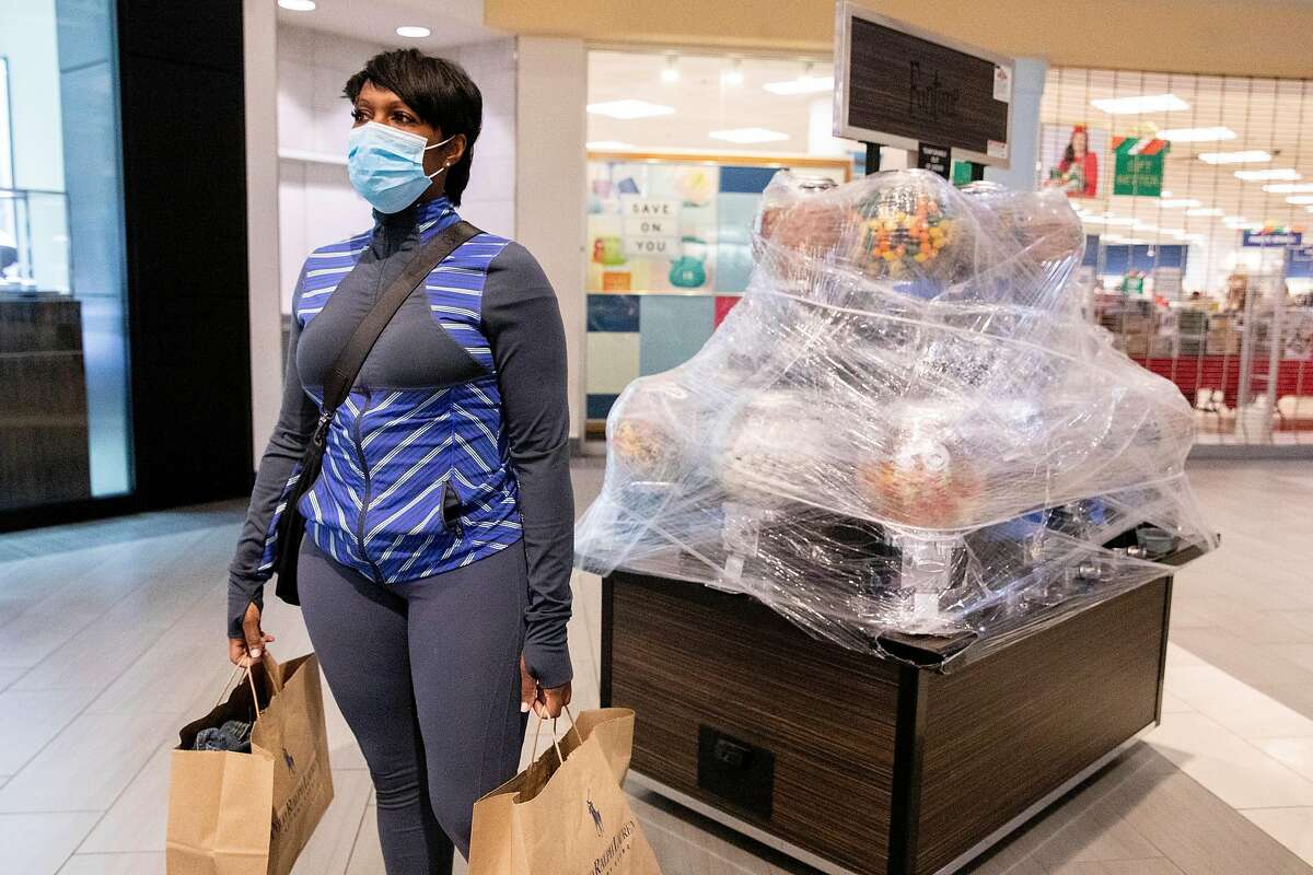 Michelle Michaels of Antioch wears a mask while carrying bags of items she bought form Ralph Lauren on Black Friday at the Great Mall in Milpitas.