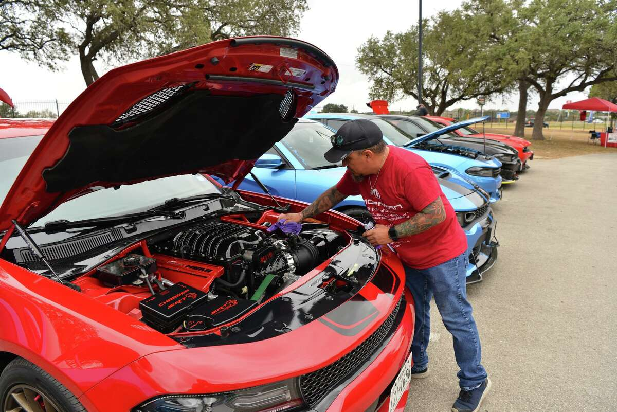 Manuel Soliz wipes down his Dodge Charger Hellcat during 'cruise in' attended by the Alamo City LX Modern Mopar, a car club, on a recent Saturday morning at 247 Church on the North Side. Older car meet enthusiasts have become irritated by a more reckless and confrontational culture they say social media has encouraged among younger drivers.