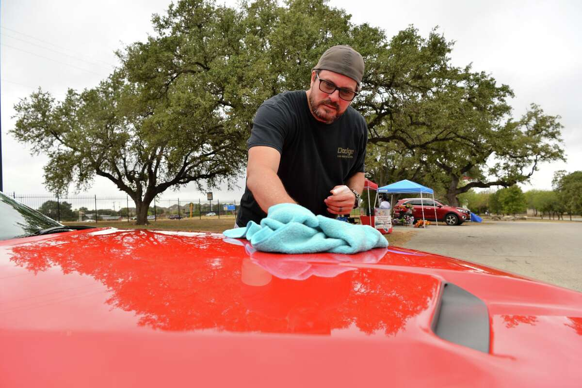 Philip Walls wipes his car during 'cruise in' attended by the Alamo City LX Modern Mopar, a car club, on a recent Saturday morning at 247 Church on the North Side. Older car meet enthusiasts have become irritated by a more reckless and confrontational culture they say social media has encouraged among younger drivers.