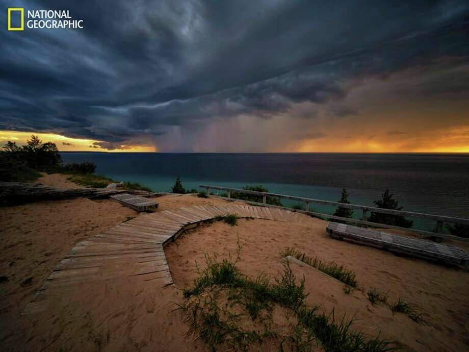 Lake Michigan-As the sun sets, a curtain of rain descends from storm clouds near Sleeping Bear Dunes National Lakeshore on the northeastern coast of Lake Michigan. Of the five Great Lakes, only Lake Michigan lies entirely within the United States. (Keith Ladzinski/National Geographic) / Image protected by copyright. For usage details and restrictions, contact National Geographic Image Collection. Email: ngimagecollection@natgeo.com or www.NatGeoImageCollection.com