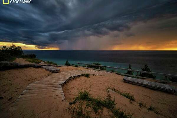 Lake Michigan-As the sun sets, a curtain of rain descends from storm clouds near Sleeping Bear Dunes National Lakeshore on the northeastern coast of Lake Michigan. Of the five Great Lakes, only Lake Michigan lies entirely within the United States. (Keith Ladzinski/National Geographic)
