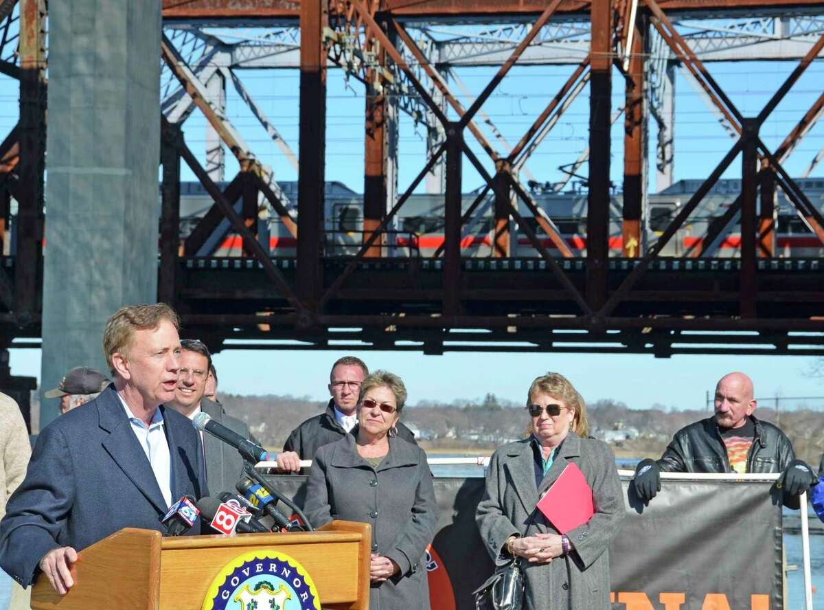 Governor Ned Lamont talks about needed transportation infrastructure improvements Monday, March 18, on Naugatuck Avenue in Milford. The focus of the talk was the Devon Bridge, in the distance, which carries New Haven line trains over the Housatonic River.