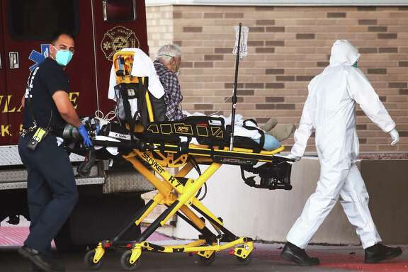 A medical worker helps transport a patient into University Medical Center amid a surge of COVID-19 cases in El Paso. Texas surpassed 20,000 confirmed coronavirus deaths, the second highest in the U.S., with active cases in El Paso now over 34,000 and confirmed more than 1,000 COVID-19 deaths.