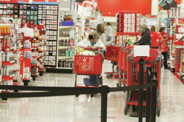A lone shopper heads toward the checkout in the Alton Target store Friday morning. Black Friday, the traditional start to the holiday shopping season, saw far fewer people hitting the stores because of the ongoing coronavirus pandemic. However, that was in part by design, as stores have emphasized online sales, and also spread out Black Friday sales through the entire month of November.