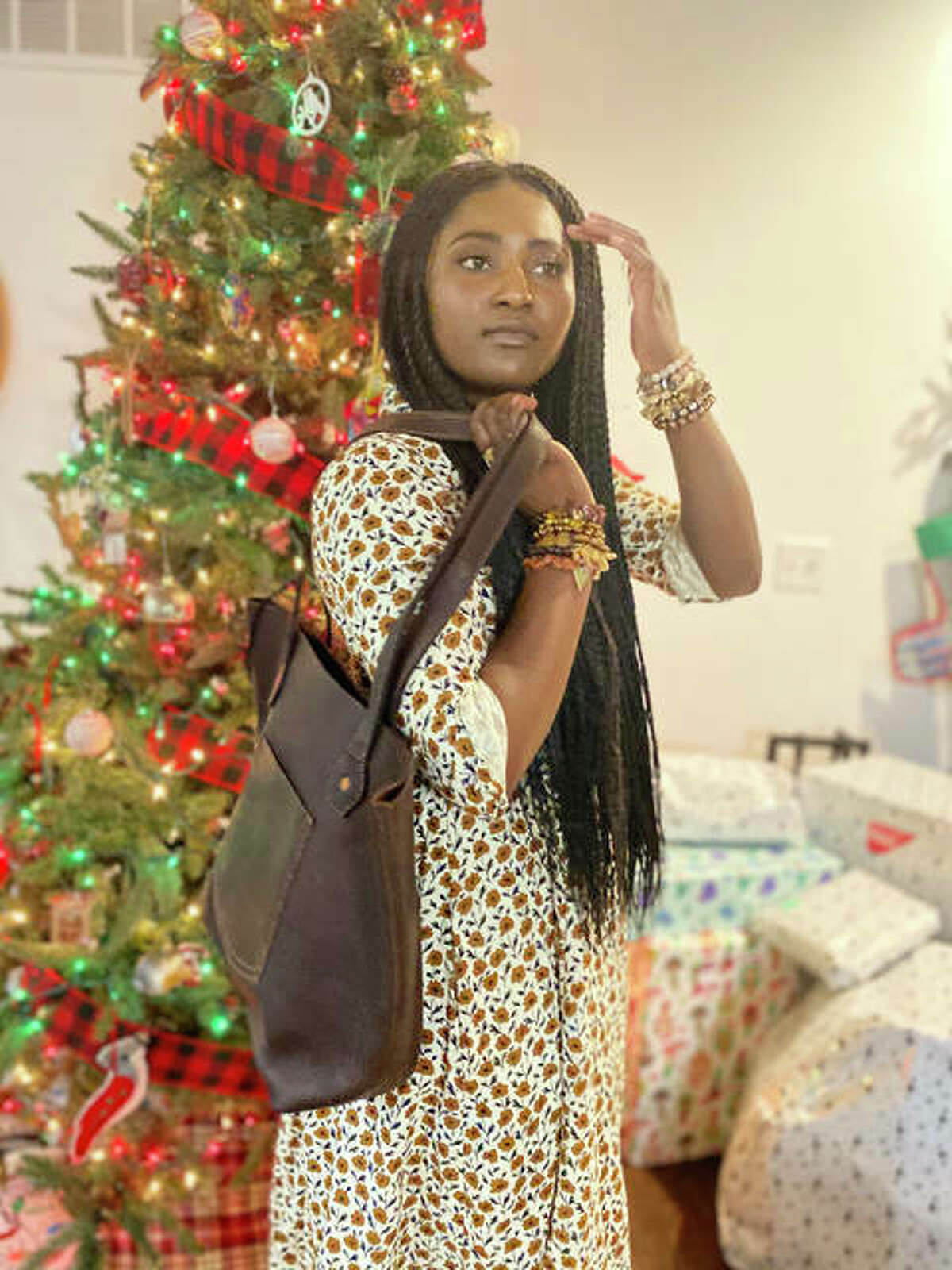 Eliana McBee, 23, a native of Haiti who lives with her husband in Godfrey, near her parents, Natalie and Michael Runyon, and nine siblings, two of whom the Runyons also adopted from Haiti, shows a bag from Haiti Made. Every sale at the annual Gifts That Give Hope Holiday Pop-Up helps women business owners stay employed and out of poverty.