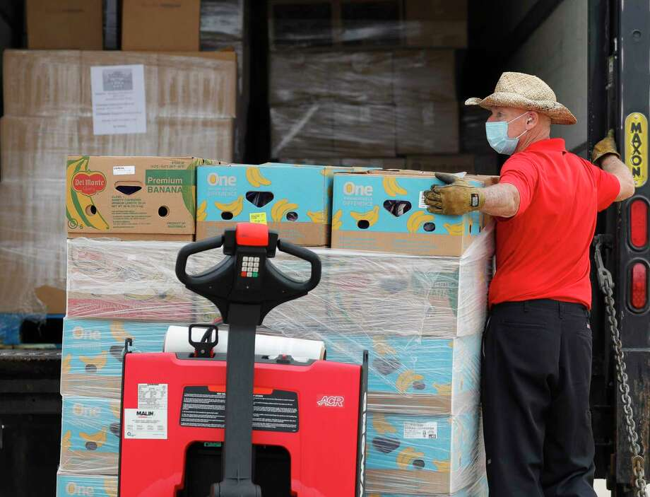 Bill Forschler helps unload fruit as volunteers with Communities in Schools staff one of Montgomery County Food Bank's COVID-19 Mobile Markets at Stockton Junior High Nov. 20. The Rotary Club of Conroe is collecting non-perishable food items for The Montgomery County Food Bank. The collection bins are located in the lobby of Honor Cafe in downtown Conroe and will continue through Dec. 9. Photo: Jason Fochtman, Houston Chronicle / Staff Photographer / 2020 © Houston Chronicle