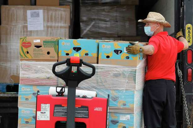Bill Forschler helps unload fruit as volunteers with Communities in Schools staff one of Montgomery County Food Bank's COVID-19 Mobile Markets at Stockton Junior High Nov. 20. The Rotary Club of Conroe is collecting non-perishable food items for The Montgomery County Food Bank. The collection bins are located in the lobby of Honor Cafe in downtown Conroe and will continue through Dec. 9.