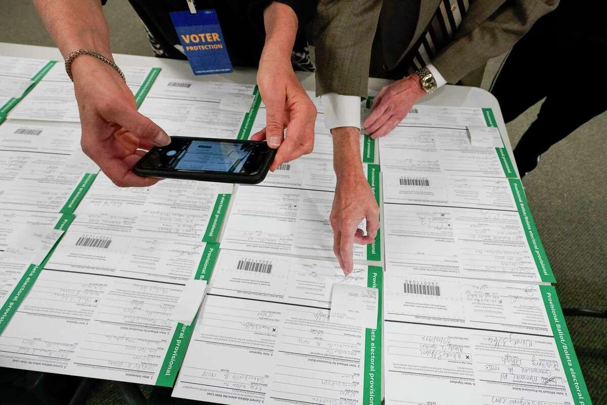 A canvas observer photographs provisional ballots in Allentown, Pennsylvania.